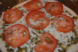 Tomato layer on pesto pizza.