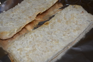 Cut focaccia in half lengthwise and spread butter with minced garlic on top.