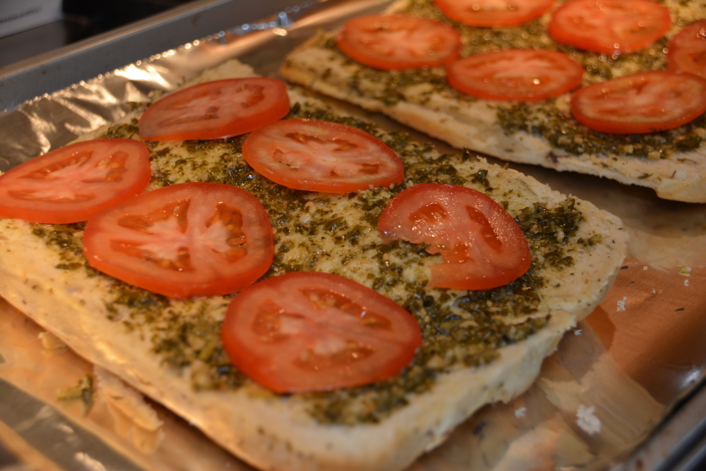 Add tomato slices on top of pesto layer.